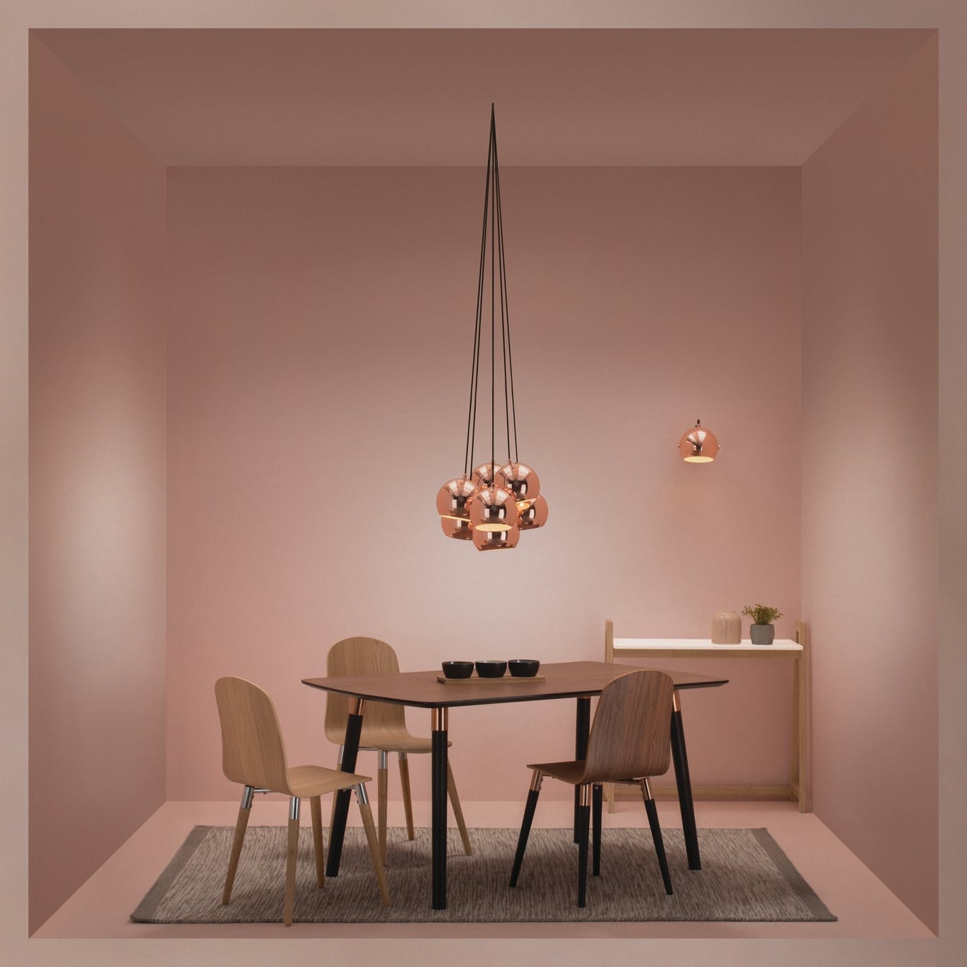 Copper hanging lamps in a pink-themed room