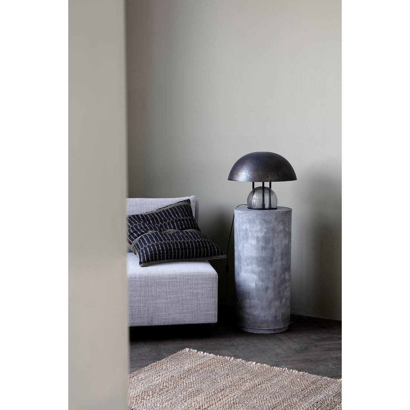 Bruno table lamp in antique brown sitting on top of small side table next to grey armchair