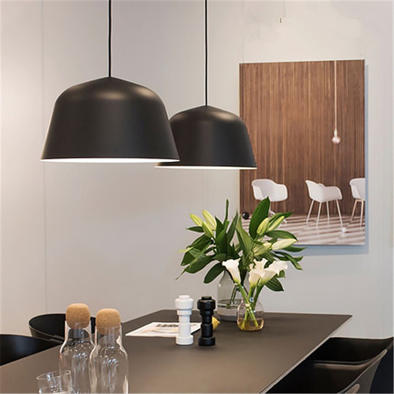 Black pendant lamps hanging above dining table
