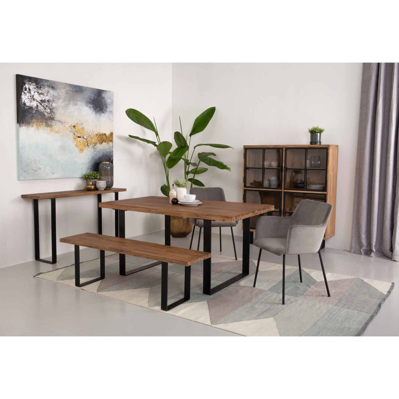 Wooden dining table placed above a geometric rug